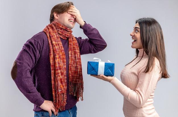 バレンタインデーの若いカップルは、白い背景で隔離された後悔した男にギフトボックスを与える興奮した女の子