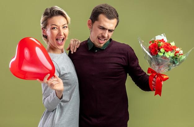 バレンタインデーの若いカップルは、オリーブグリーンの背景に分離された花束と男の肩に手を置いてハートバルーンを保持している女の子を興奮させた