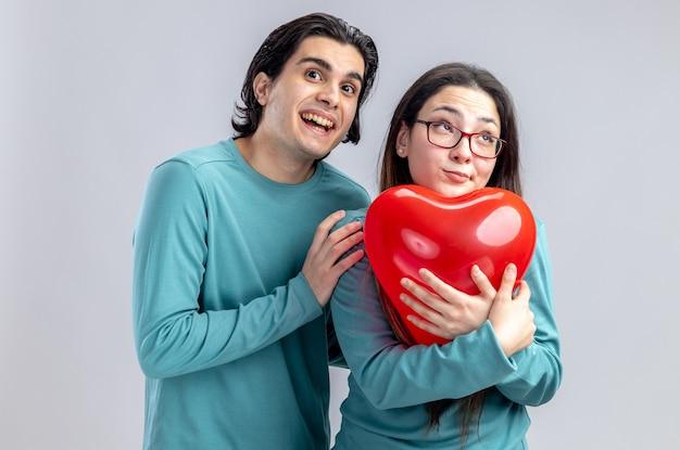 발렌타인 데이에 젊은 부부는 흰색 배경에 고립 된 하트 풍선으로 여자를 껴안은 흥분된 남자