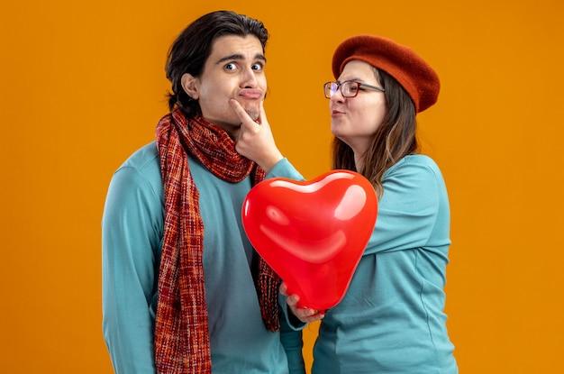 オレンジ色の背景で隔離の彼のあごに手を置くハートバルーンを保持している帽子をかぶってバレンタインデーの少女の若いカップル
