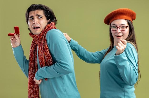 Молодая пара на день святого валентина парень в шарфе девушка в шляпе испуганный парень дарит обручальное кольцо довольной девушке, изолированной на оливково-зеленом фоне