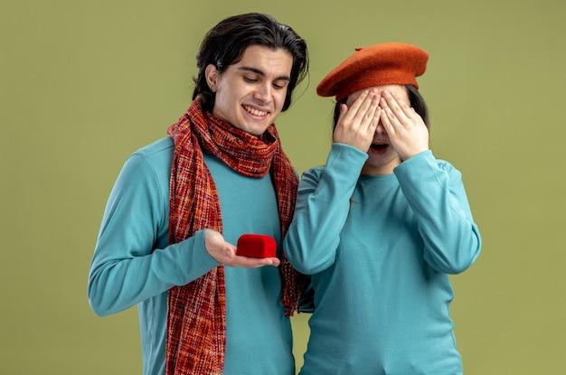 Молодая пара на день святого валентина парень в шарфе девушка в шляпе улыбающийся парень дает обручальное кольцо девушке, изолированной на оливково-зеленом фоне