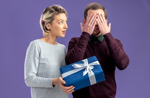 バレンタインデーの若いカップルは、青い背景で隔離の男にギフトボックスを与える女の子を喜ばせます
