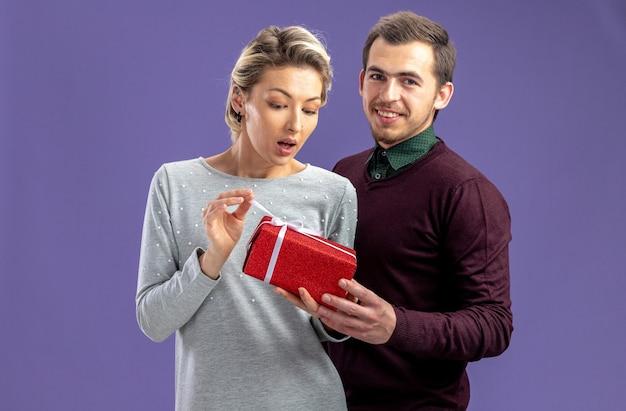 バレンタインデーの若いカップルは、青い背景で隔離の驚いた女の子にギフトボックスを与える男を喜ばせた