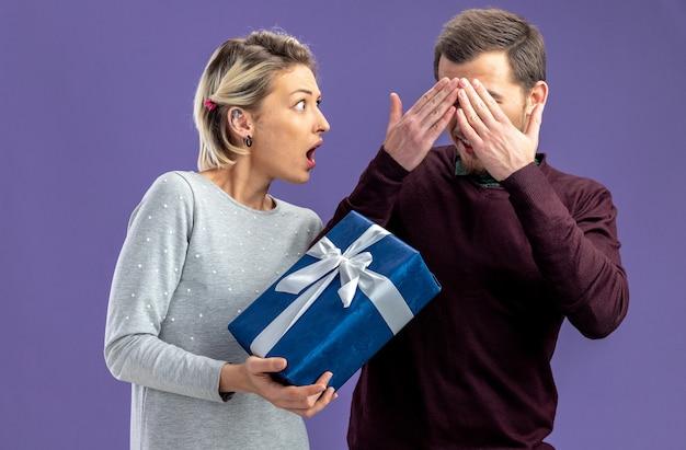 バレンタインデーの若いカップルは、青い背景で隔離の男にギフトボックスを与える女の子を怖がらせた