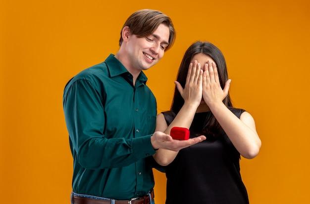 Молодая пара на день святого валентина улыбающийся парень дарит обручальное кольцо девушке, изолированной на оранжевом фоне