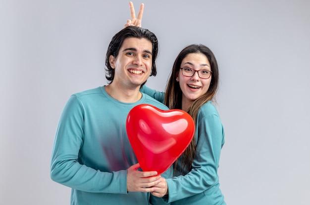 발렌타인 데이에 젊은 부부는 흰색 배경에 고립 된 심장 풍선 남자를 위해 토끼 귀 제스처를 하 고 웃는 소녀