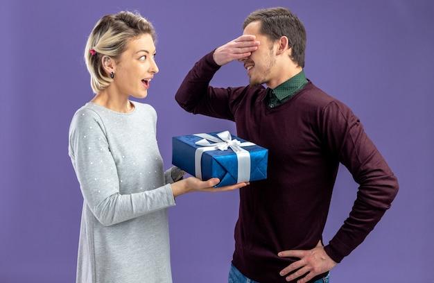 青い背景で隔離の男にギフトボックスを与えるバレンタインデーの笑顔の若いカップル
