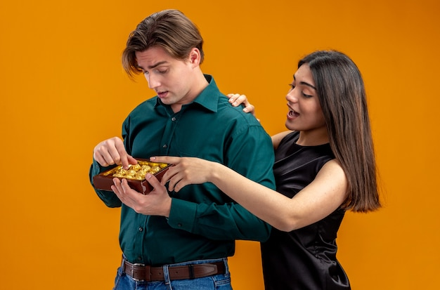 オレンジ色の背景で隔離の杖の箱を持つ男の隣に立っているバレンタインデーの笑顔の女の子の若いカップル