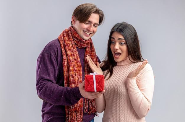 白い背景で隔離の驚いた女の子にギフトボックスを与えるバレンタインデーの笑顔の若いカップル