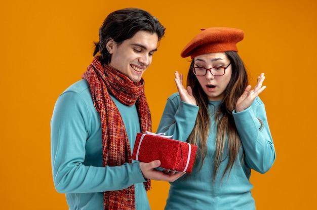 オレンジ色の背景で隔離の女の子にギフトボックスを与えるスカーフを身に着けている男笑顔のバレンタインデーの若いカップル