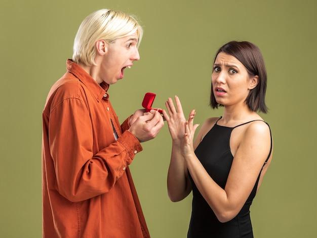 프로필 보기에 서 있는 발렌타인 데이에 젊은 부부는 약혼 반지를 주는 흥분된 남자