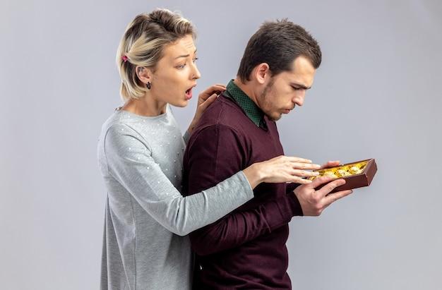 バレンタインデーの若いカップルは、白い背景で隔離のキャンディーの箱を持つ男の隣に立っている女の子を驚かせた