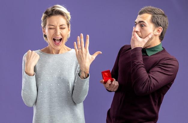 バレンタインデーの若いカップルは、青い背景で隔離の興奮した女の子に結婚指輪を与える男を驚かせた