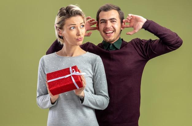 バレンタインデーの若いカップルは、オリーブグリーンの背景で隔離の女の子の閉じた耳の後ろに立っているギフトボックス笑顔の男を保持