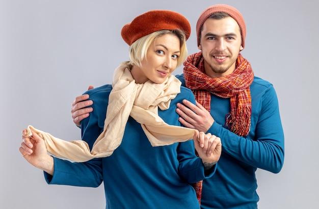 バレンタインデーの若いカップルは、白い背景で隔離のスカーフ男抱きしめた女の子を保持しているスカーフ喜んでいる女の子と帽子をかぶっています