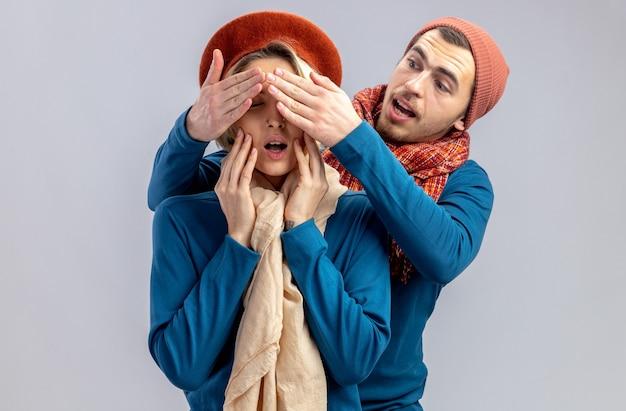 白い背景で隔離の女の子の目を覆ったスカーフ笑顔の男と帽子をかぶってバレンタインデーの若いカップル