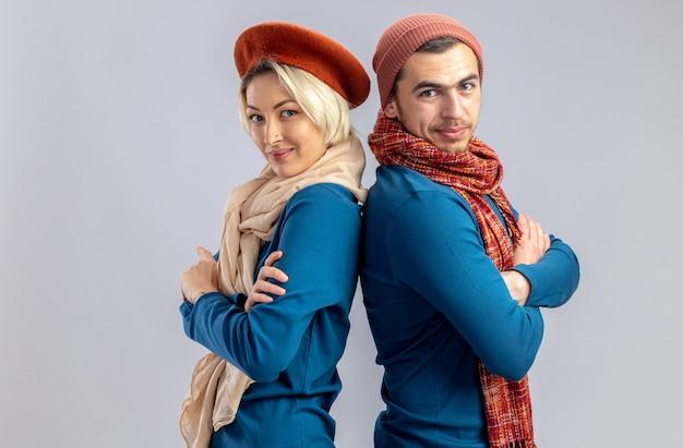 白い背景で隔離のスカーフと背中合わせに立っている帽子をかぶってバレンタインデーの若いカップル