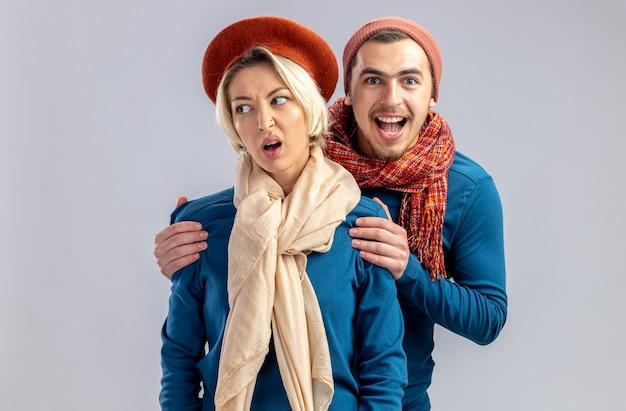 발렌타인 데이에 젊은 부부는 스카프로 모자를 쓰고 흰색 배경에 고립 된 소녀 뒤에 서있는 옆 남자를 찾고 불쾌한 소녀