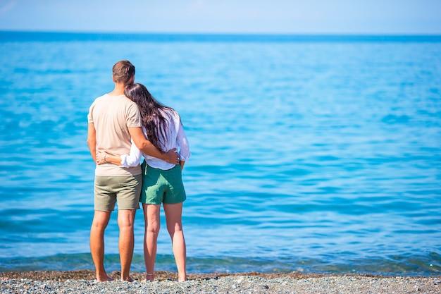Молодая пара на белом пляже во время летних каникул.