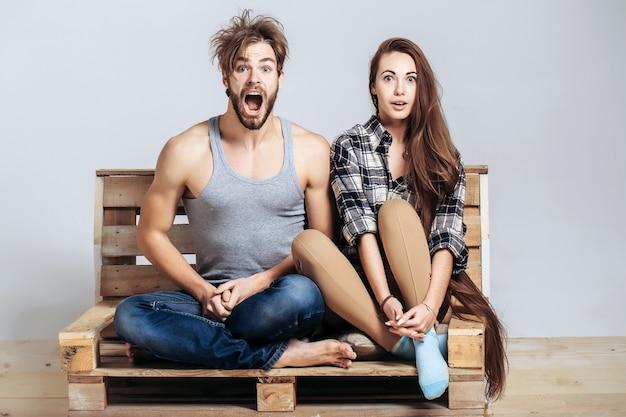 Молодая пара на деревянном диване