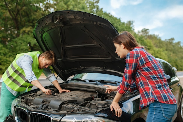 Young couple at the opened hood on road, car breakdown. broken automobile or emergency accident with vehicle, trouble with engine on highway