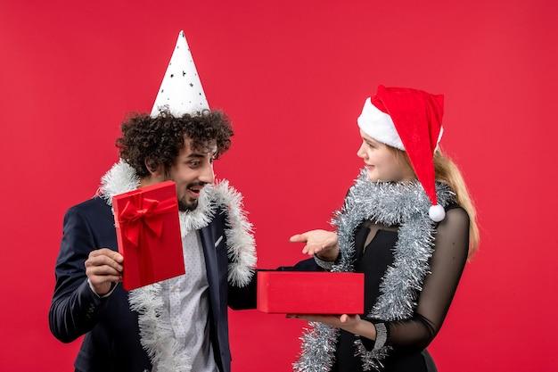 Молодая пара открывает новогодний подарок на красном полу рождественская вечеринка