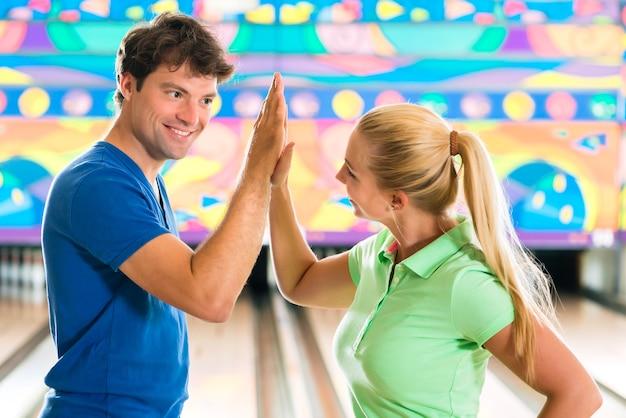 Молодая пара или друзья, мужчина и женщина, играя в боулинг перед аллеей с десятью кеглями, они - команда