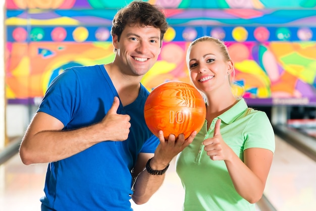 Молодая пара или друзья, мужчина и женщина, играя в боулинг с мячом перед аллеей с десятью кеглями, они - команда