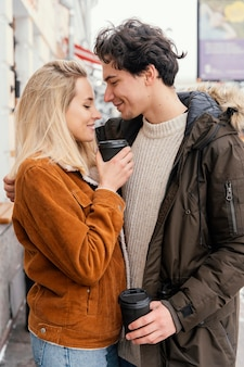 Young couple outdoor enjoying cup of coffee