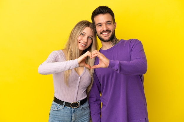 손으로 마음을 만드는 고립 된 노란색 배경 위에 젊은 부부