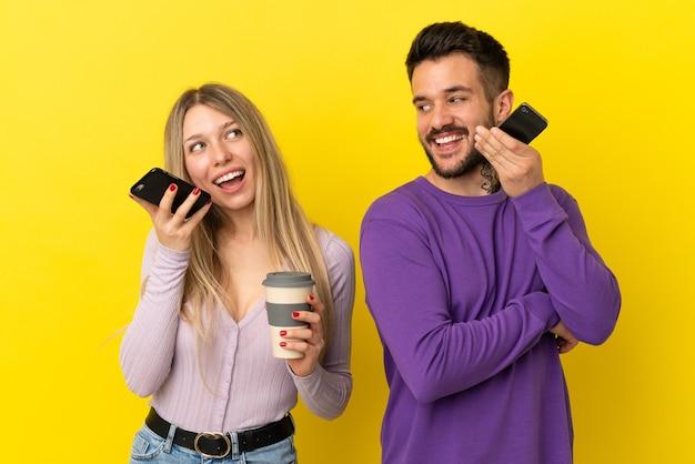격리된 노란색 배경 위에 있는 젊은 부부는 모바일로 메시지 음성이나 이메일을 보냅니다.