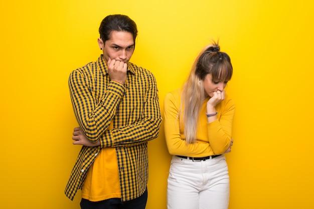 Молодая пара на ярком желтом фоне, имея сомнения