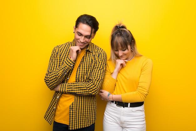 Молодая пара на ярком желтом фоне, глядя вниз