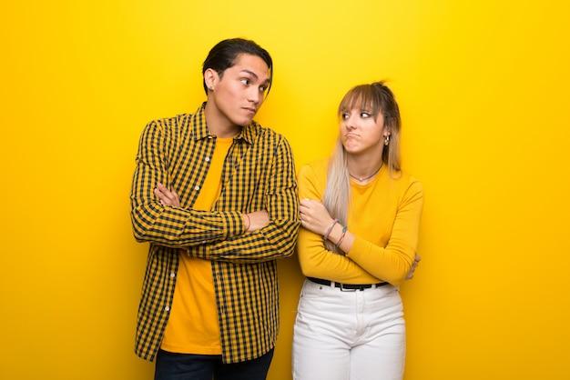 Молодая пара на ярком желтом фоне, делая сомнения жест