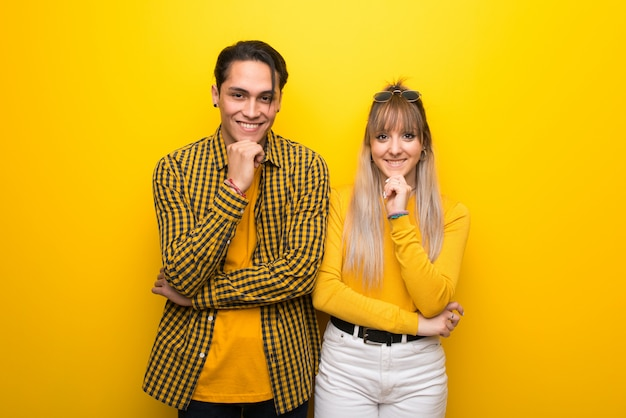 Молодая пара на ярком желтом фоне, улыбаясь и глядя на фронт