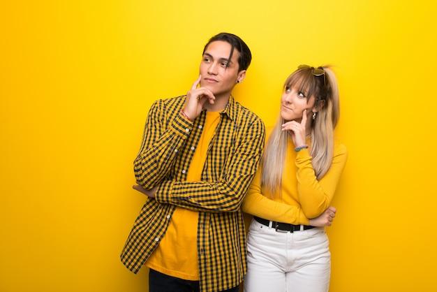 Молодая пара на ярком желтом фоне, думая, идея