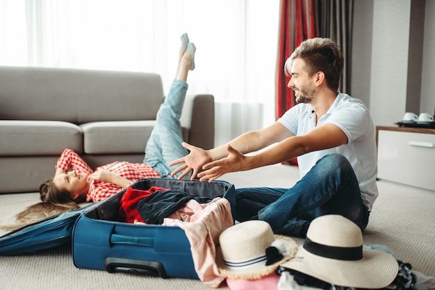 Young couple packing their suitcases for vacation