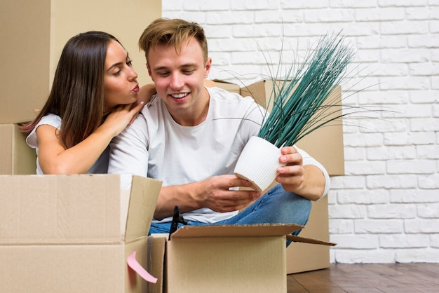Young couple packing things in boxes
