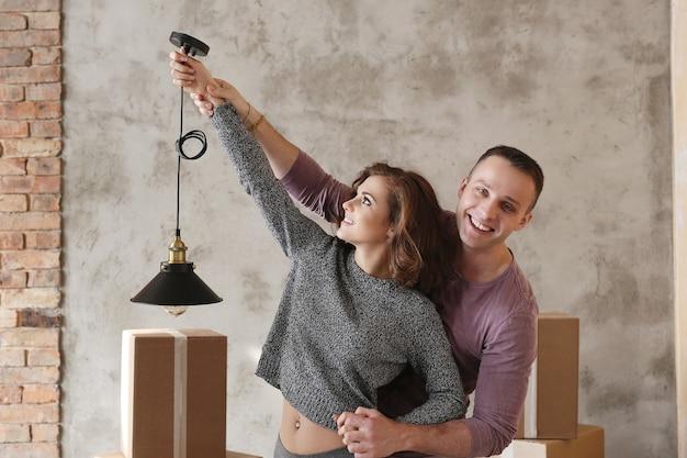 Молодая пара собирает вещи для переезда и танцует