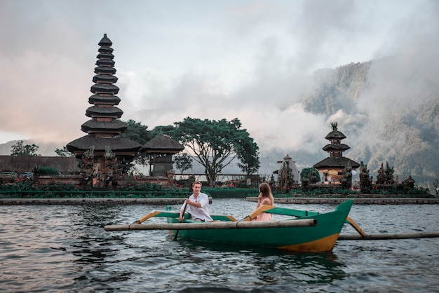 Young couple paddling on a wooden boat at pura ulun danu bratan