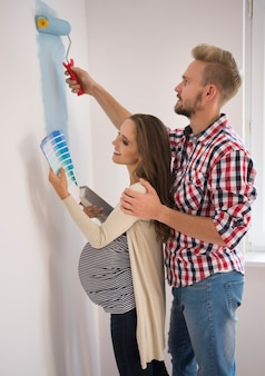 Young couple painting a blue wall