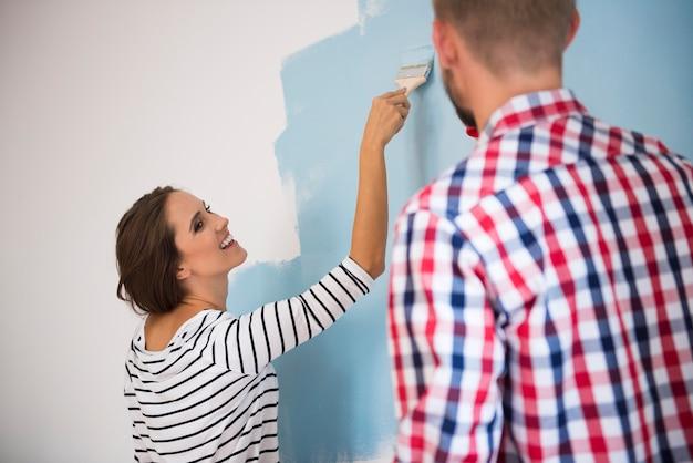 Giovani coppie che verniciano una parete blu