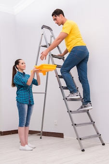Young couple painting wall at home
