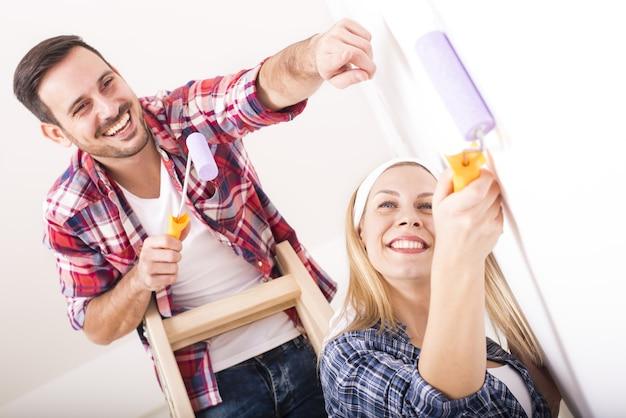 Молодая пара вместе красит стену в своем новом доме