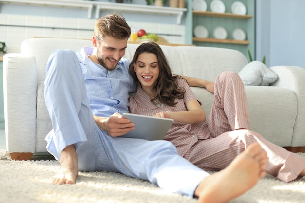 Young couple in pajamas watching media content online in a tablet sitting on the floor in the living room.