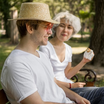 Young couple at the park eating burgers