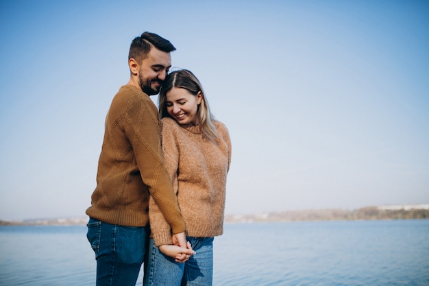 Young couple in park standing by the river