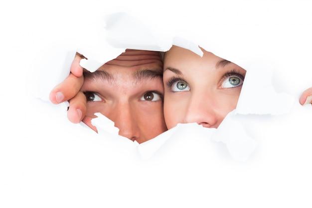 Молодая пара, выглядывающая через рваную бумагу