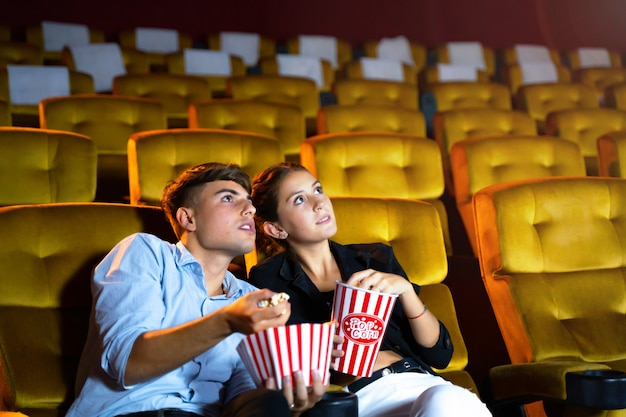 Young couple people watching movie at movie theater.